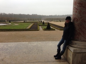 Leaning against one of the pink columns of the Grand Trianon