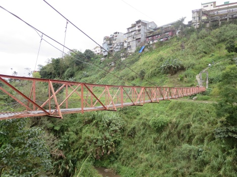 suspension bridge that straddles the river which cuts through town