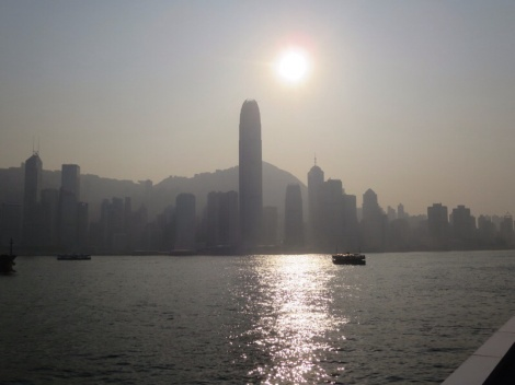 the sun begins to set over the hong kong skyline